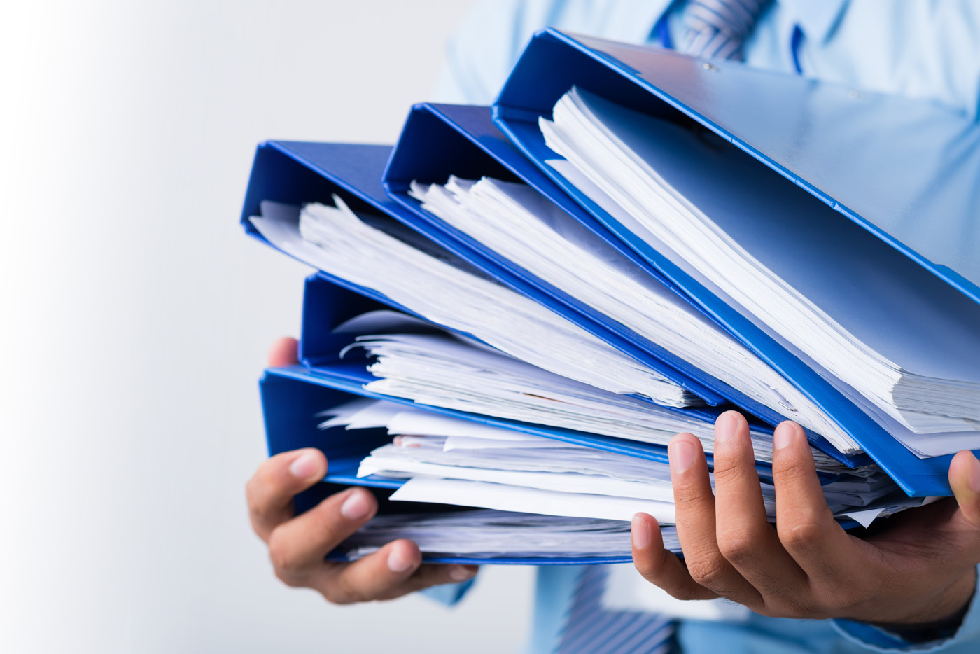 A persons holding a stack of binders